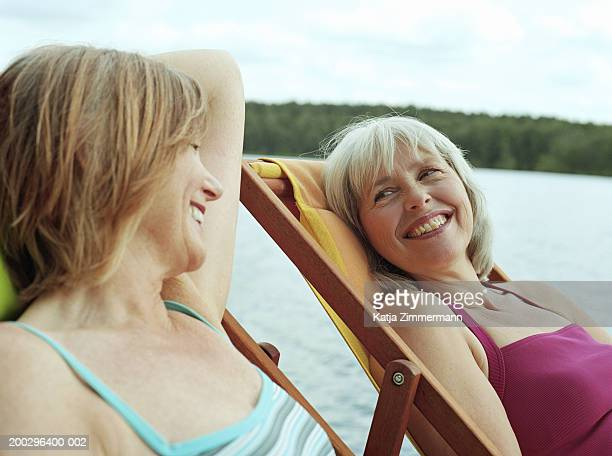Mature women relaxing in deckchairs, smiling at each other, close-up