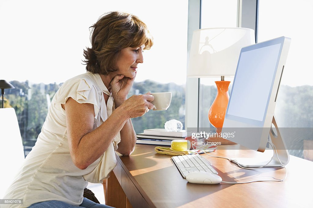 Mature women sitting in front of computer : Foto de stock