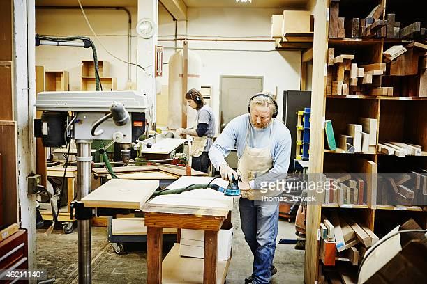 Mature woodworker in woodshop sanding panel