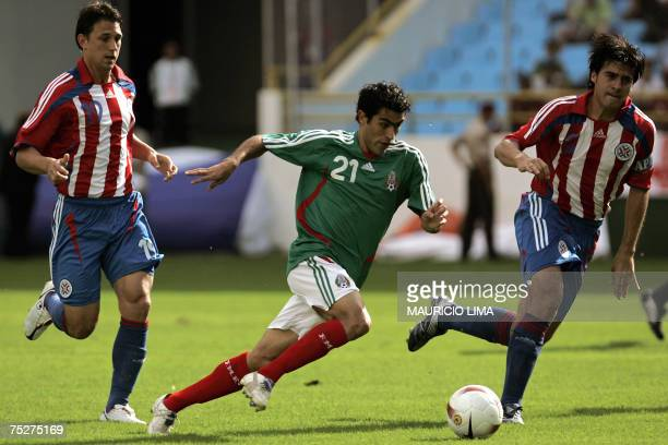 Mexico's Nery Castillo dribbles past Paraguay's Jonathan Santana and captain Julio Cesar Caceres during their Copa America 2007 quarterfinal football...