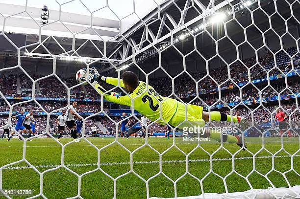 Matus Kozacik of Slovakia dives to stop the penalty kick by Mesut Oezil of Germany during the UEFA EURO 2016 round of 16 match between Germany and...