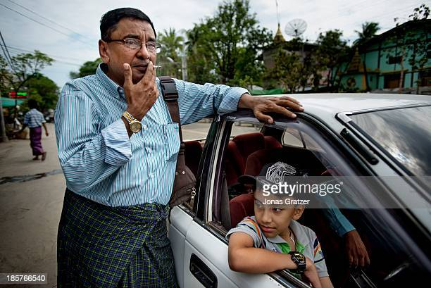 Maung Maung smokes a cigarette while his son sits and waits in their car in the city of Mandalay After living in constant fear of a Buddhist attack U...