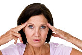Mature woman isolated on white and rubbing her temples lease for a headache concept