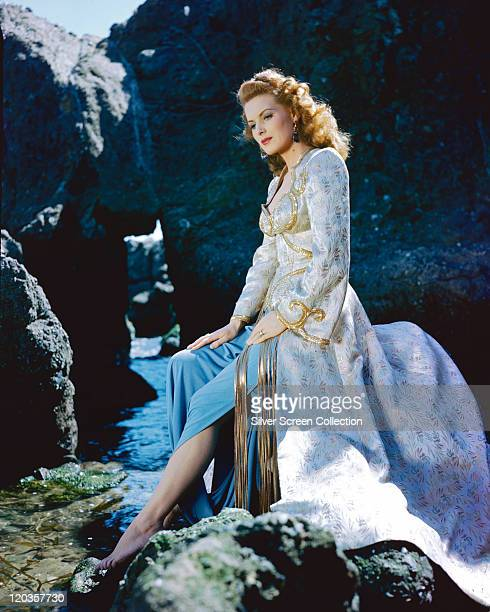 Maureen O'Hara Irish actress wearing a pale blue gold brocade jacket with a blue skirt sitting barefoot on a rock circa 1950