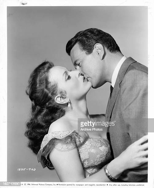 Maureen O'Hara is kissed by John Forsythe in publicity portrait for the film 'Everything But The Truth' 1956