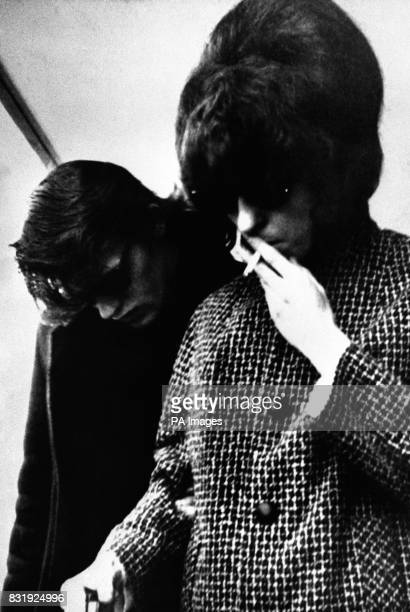 Maureen Smith sister of one of the accused smokes a cigarette as she is escorted by her husband David Smith when the hearing resumed