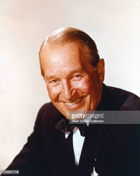 Maurice Chevalier French actor singer and vaudeville entertainer wearing a black jacket a white shirt and a black bow tie and smiling in a studio...