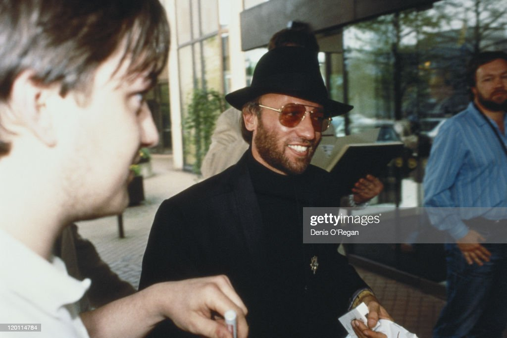 Maurice Gibb (1949 - 2003) of the Bee Gees, signs autographs for fans, circa 1990.