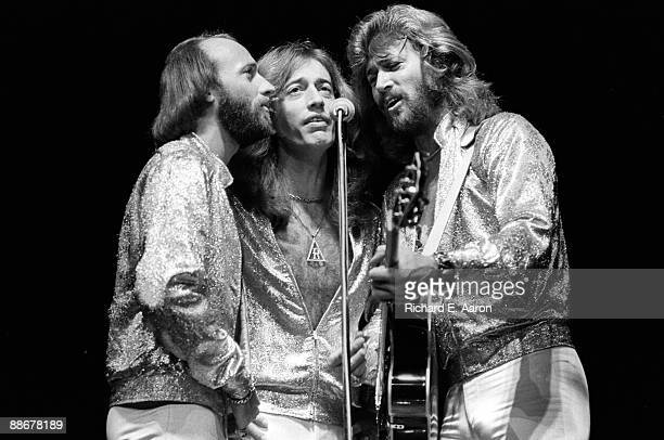 Maurice Gibb Robin Gibb and Barry Gibb of The Bee Gees harmonising around a microphone while performing on stage at Madison Square Garden on the...