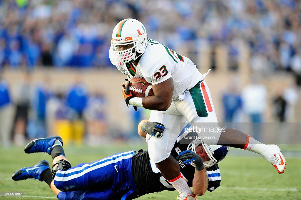 Maurice Hagens #33 of the Miami Hurricanes breaks a tackle by Kyler Brown #56 of the Duke Blue Devils during play at Wallace Wade Stadium on November 16, 2013 in Durham, North Carolina.