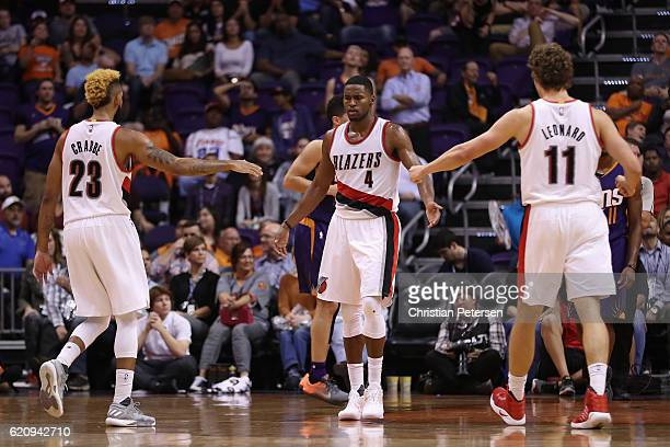 Maurice Harkless of the Portland Trail Blazers high fives Allen Crabbe and Meyers Leonard after scoring against the Phoenix Suns during overtime of...