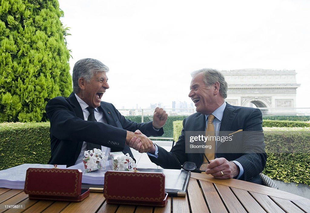 Maurice Levy, chief executive officer of Publicis Groupe SA, left, and John Wren, chief executive officer of Omnicom Group Inc., shake hands on the merger during a news conference held on the rooftop of the Publicis headquarters in Paris, France, on Sunday, July 28, 2013. Publicis Groupe SA and Omnicom Group Inc. agreed to merge in an all-stock transaction to create the world's largest advertising company with $23 billion in revenue, toppling market leader WPP Plc. Photographer: Balint Porneczi/Bloomberg via Getty Images