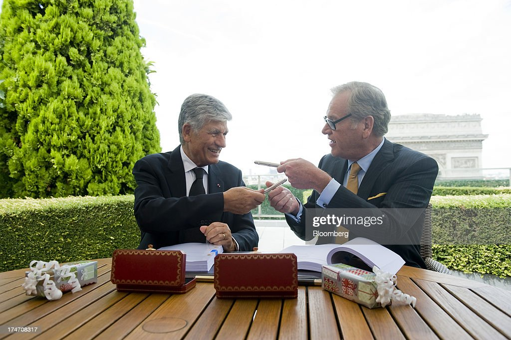 Maurice Levy, chief executive officer of Publicis Groupe SA, left, and John Wren, chief executive officer of Omnicom Group Inc., exchange pens while signing the merger during a news conference held on the rooftop of the Publicis headquarters in Paris, France, on Sunday, July 28, 2013. Publicis Groupe SA and Omnicom Group Inc. agreed to merge in an all-stock transaction to create the world's largest advertising company with $23 billion in revenue, toppling market leader WPP Plc. Photographer: Balint Porneczi/Bloomberg via Getty Images