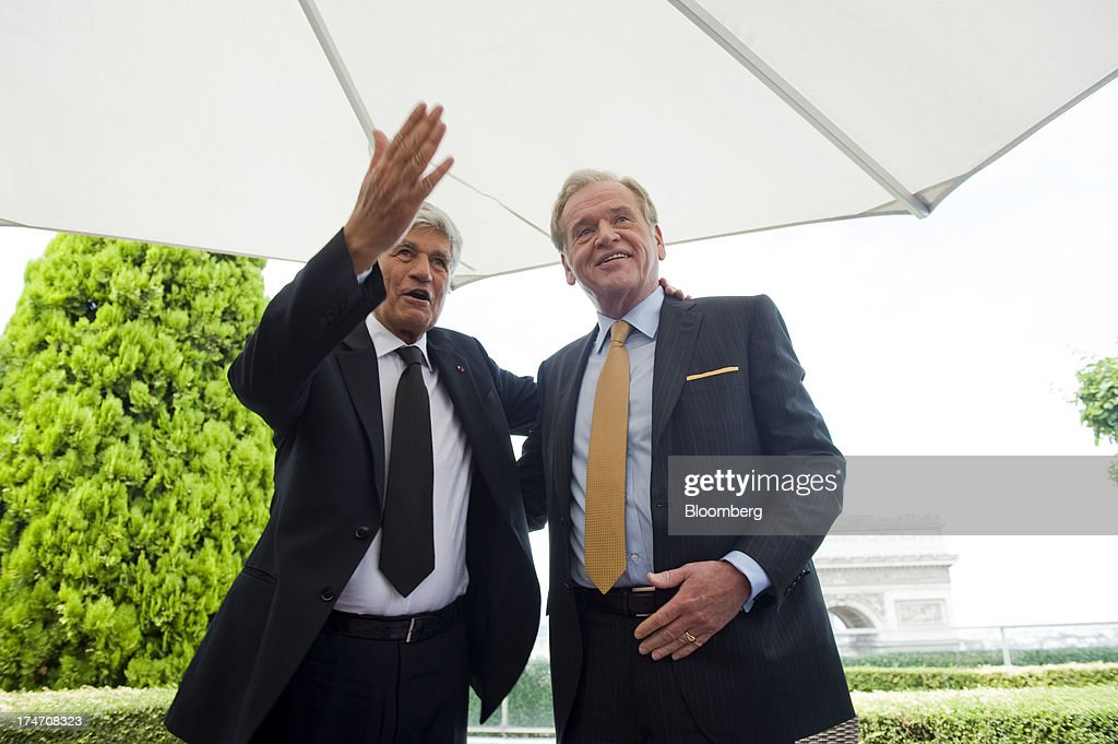 Maurice Levy, chief executive officer of Publicis Groupe SA, left, and John Wren, chief executive officer of Omnicom Group Inc., celebrate after signing the merger during a news conference held on the rooftop of the Publicis headquarters in Paris, France, on Sunday, July 28, 2013. Publicis Groupe SA and Omnicom Group Inc. agreed to merge in an all-stock transaction to create the world's largest advertising company with $23 billion in revenue, toppling market leader WPP Plc. Photographer: Balint Porneczi/Bloomberg via Getty Images