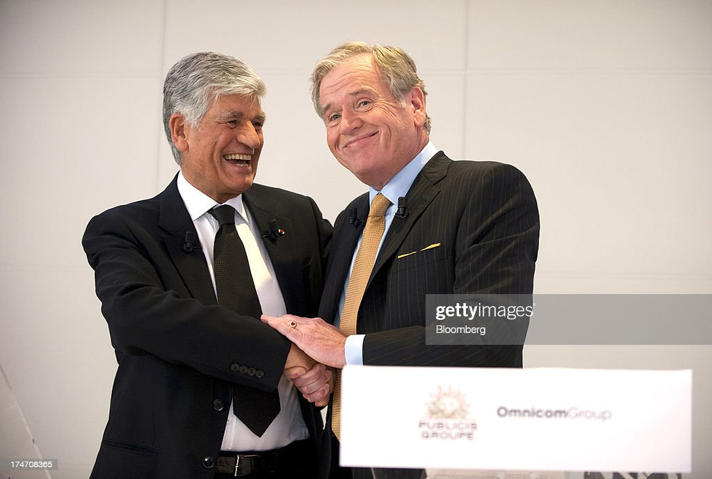 Maurice Levy, chief executive officer of Publicis Groupe SA, left, and John Wren, chief executive officer of Omnicom Group Inc., shake hands after signing the merger deal during a news conference at the Publicis headquarters in Paris, France, on Sunday, July 28, 2013. Publicis Groupe SA and Omnicom Group Inc. agreed to merge in an all-stock transaction to create the world's largest advertising company with $23 billion in revenue, toppling market leader WPP Plc. Photographer: Balint Porneczi/Bloomberg via Getty Images
