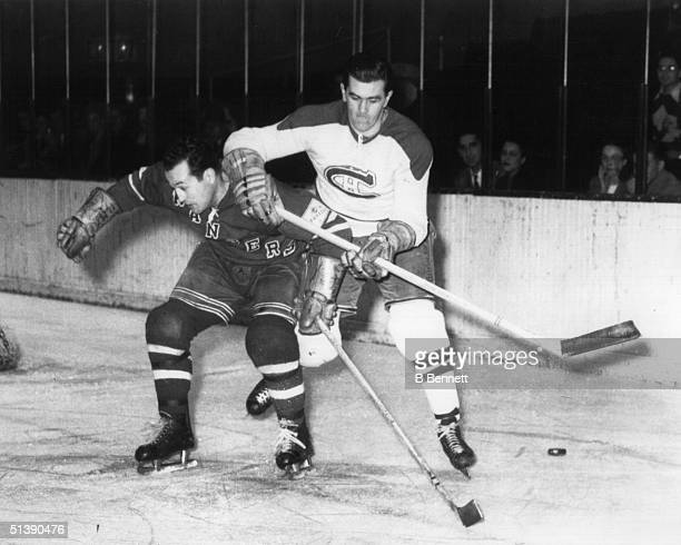 Maurice Richard of the Montreal Canadiens battles with Edgar Laprade of the New York Rangers during an NHL game circa 1950 at Madison Square Garden...