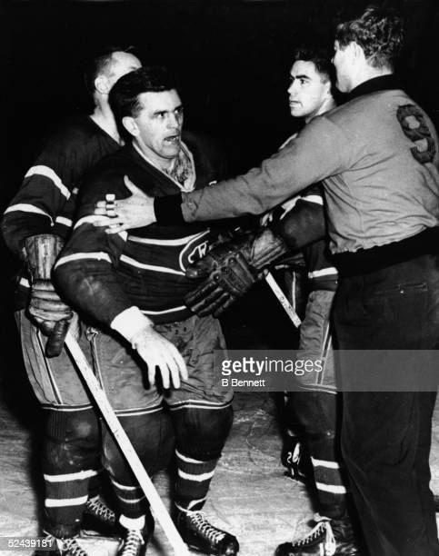 Maurice 'Rocket' Richard of the Montreal Canadiens is restrained by linesman George Hayes after Richard was boarded by Bob Bailey of the Toronto...