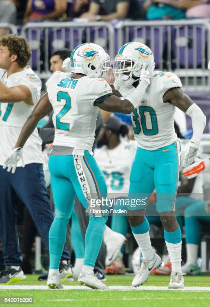 Maurice Smith and Cordrea Tankersley of the Miami Dolphins celebrate an incomplete pass against the Minnesota Vikings in the preseason game on August...