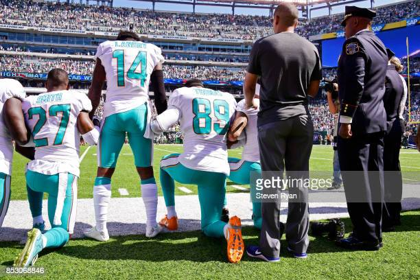 Maurice Smith and Julius Thomas kneel with Jarvis Landry of the Miami Dolphins during the National Anthem prior to an NFL game against the New York...