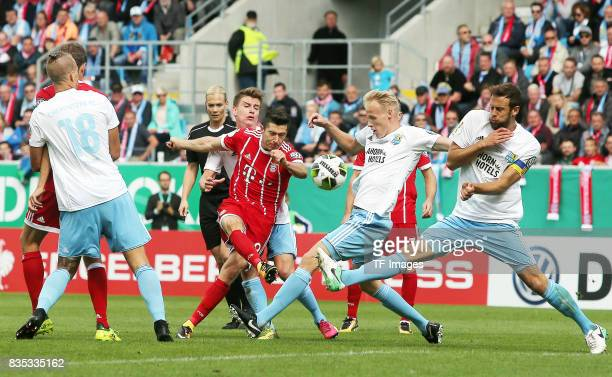 Maurice Trapp of Chemnitz and Robert Lewandowski of Bayern Muenchen and Tom Scheffel of Chemnitz battle for the ball during the DFB Cup first round...