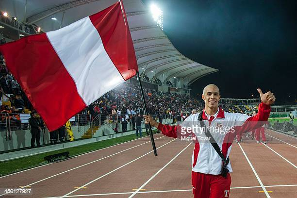 Mauricio Fiol athlete of Peru holds on the flag during the inauguration day of the XVII Bolivarian Games Trujillo 2013 at Chan Chan Stadium on...
