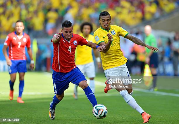 Mauricio Isla of Chile and Luiz Gustavo of Brazil compete for the ball during the 2014 FIFA World Cup Brazil round of 16 match between Brazil and...