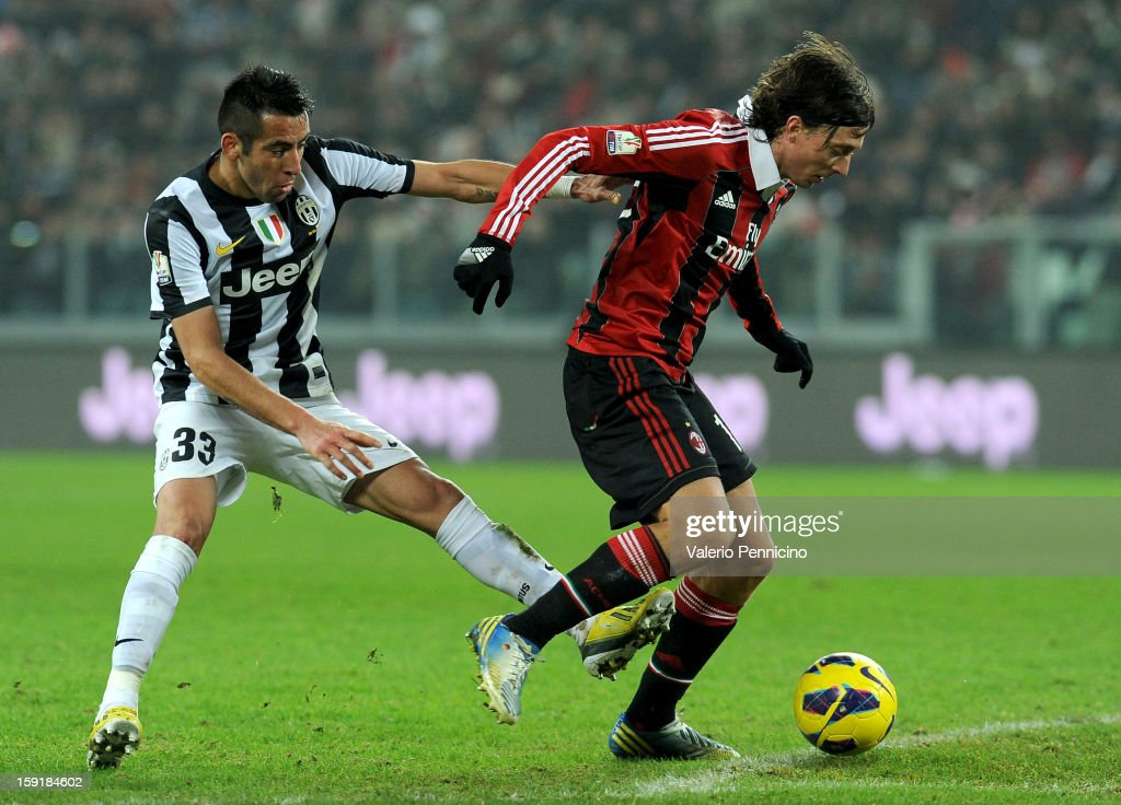 Mauricio Isla (L) of Juventus FC competes with Riccardo Montolivo of AC Milan during the TIM cup match between Juventus FC and AC Milan at Juventus Arena on January 9, 2013 in Turin, Italy.