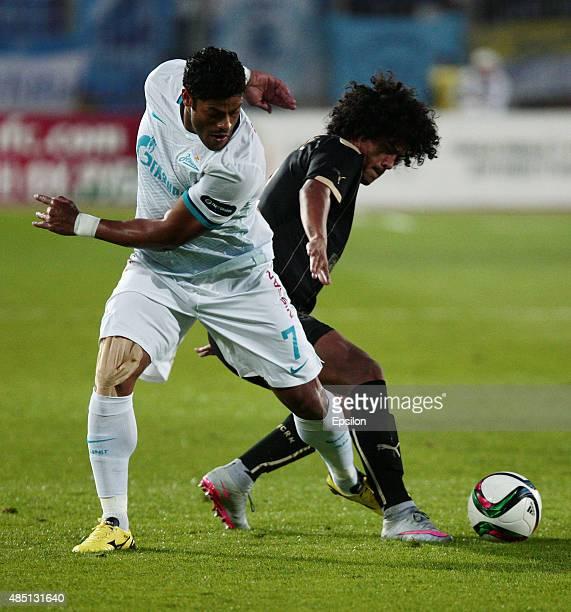 Mauricio Lemos of FC Rubin Kazan is challenged by Hulk of FC Zenit Saint Petersburg during the Russian Premier League match between FC Rubin Kazan...