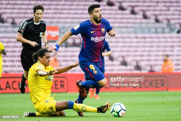 Mauricio Lemos of UD Las Palmas trips up with Luis Alberto Suarez Diaz of FC Barcelona during the La Liga 201718 match between FC Barcelona and Las...