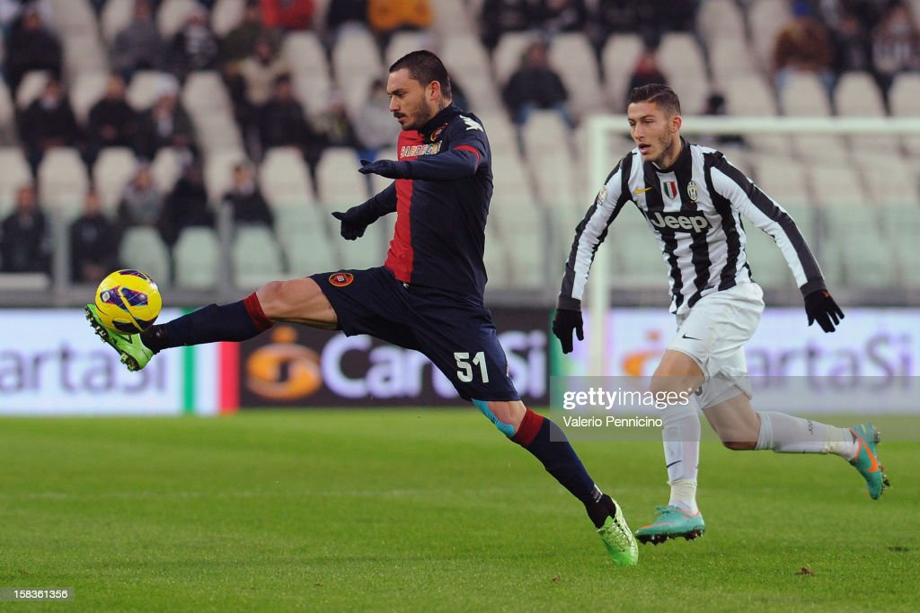 Mauricio Pinilla (L) of Cagliari Calcio reaches the ball ahead of Luca Marrone of Juventus FC during the TIM Cup match between Juventus FC and Cagliari Calcio at Juventus Arena on December 12, 2012 in Turin, Italy.