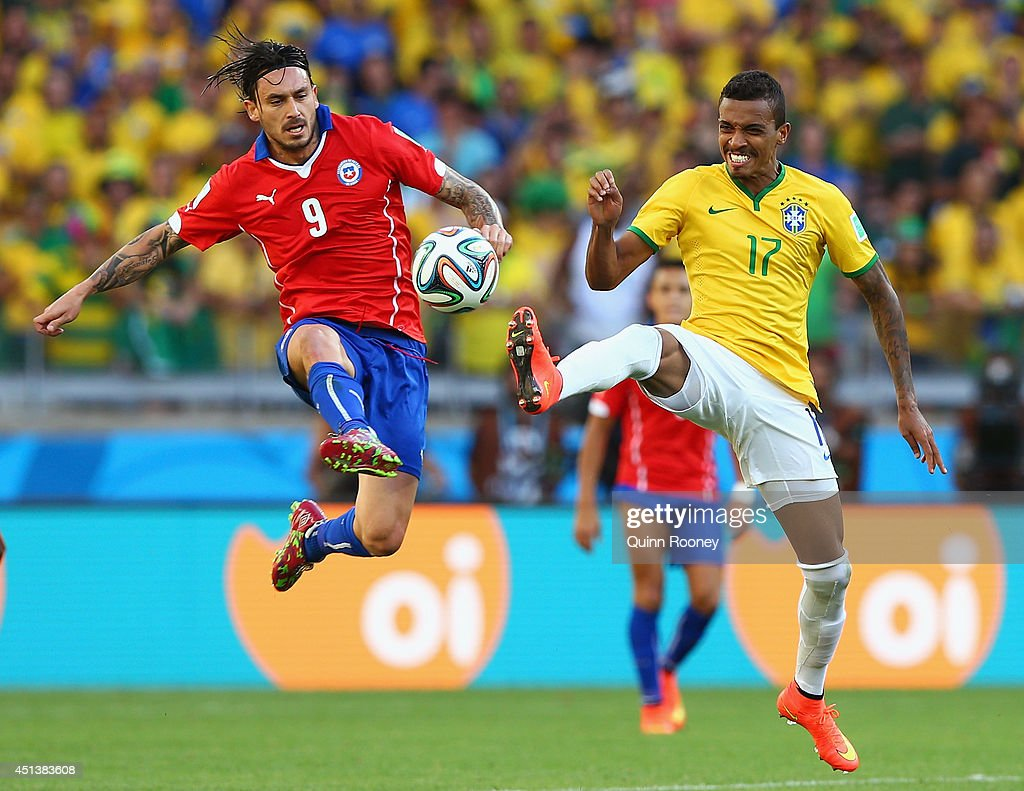 Mauricio Pinilla of Chile and Luiz Gustavo of Brazil compete for the ball during the 2014 FIFA World Cup Brazil round of 16 match between Brazil and...