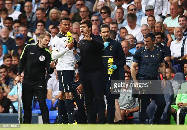 Mauricio Pochettino Manager of Tottenham Hotspur gives Dele Alli of Tottenham Hotspur insturstions while he has a drink during the Premier League...