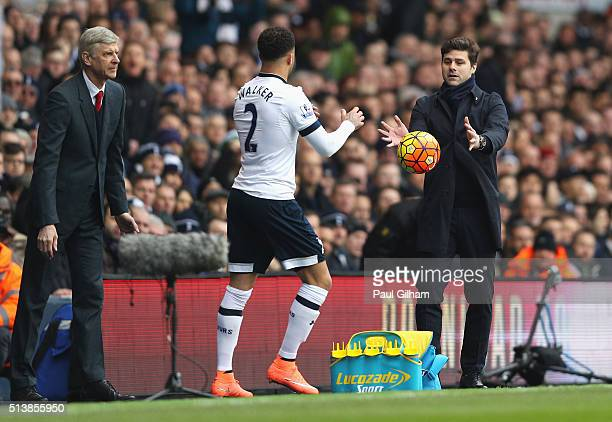 Mauricio Pochettino Manager of Tottenham Hotspur throws the ball to Kyle Walker of Tottenham Hotspur as Arsene Wenger manager of Arsenal looks on...