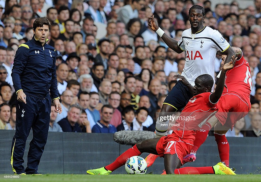 Mauricio Pochettino the Spurs manager looks on as Mamadou Sakho of Liverpool competes with Emmanuel Adebayor of Tottenham Hotspur during the Barclays Premier League match between Tottenham Hotspur and Liverpool at White Hart Lane on August 31, 2014 in London, England.