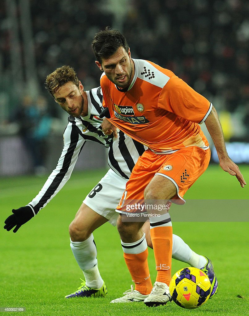 Maurizio Domizzi (R) of Udinese Calcio is pulled by his shirt by Claudio Marchisio of Juventus during the Serie A match between Juventus and Udinese Calcio at Juventus Arena on December 1, 2013 in Turin, Italy.