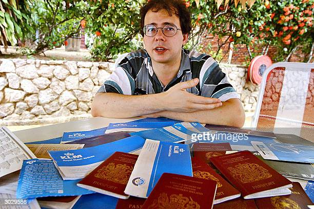 Maurizio Giuliano shows 27 February 2004 some of his passports and airline tickets at Hotel Torarica in Paramaribo The BritishItalian Giuliano claims...