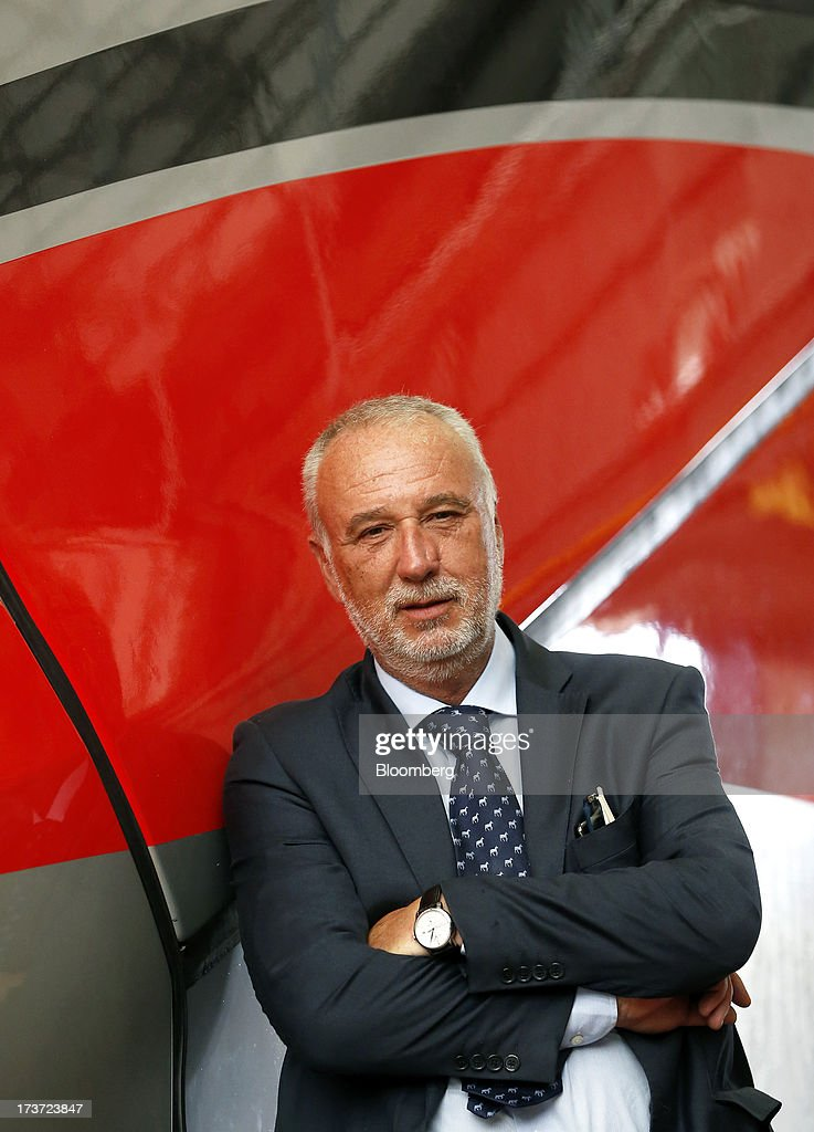 Maurizio Manfellotto, chief executive officer of AnsaldoBreda SpA, poses for a photograph in front of a Frecciarossa 1000 high-speed train at the company's rail-car plant in Pistoia, Italy, on Tuesday, July 16, 2013. Italian business confidence rose last month after Prime Minister Enrico Letta's Cabinet passed plans to boost employment and postponed the payment of the value-added tax planned for July. Photographer: Alessia Pierdomenico/Bloomberg via Getty Images