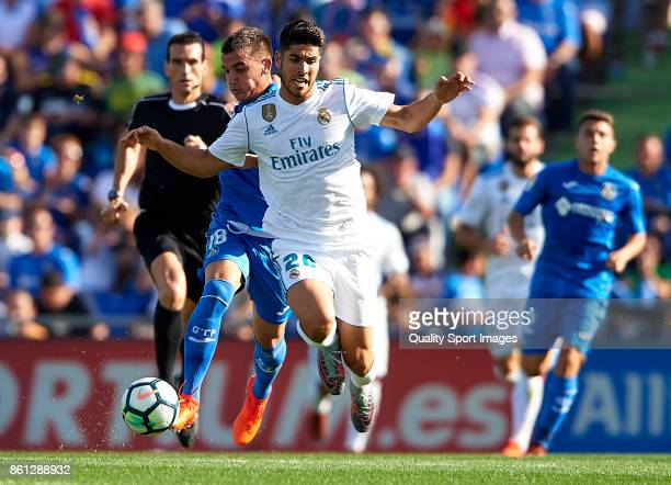 Mauro Arambarri of Getafe competes for the ball with Marco Asensio of Real Madrid during the La Liga match between Getafe and Real Madrid at Estadio...