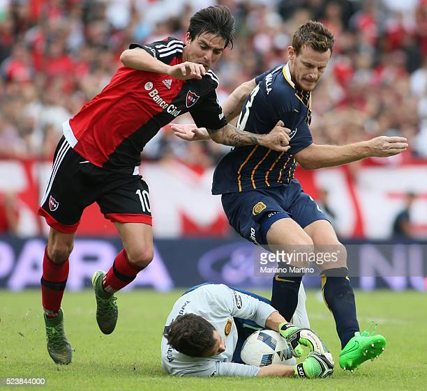Mauro Formica of Newell's fights for the ball with Mauro Cetto and Sebastian Sosa of Central during a match between Newell's Old Boys and Rosario...
