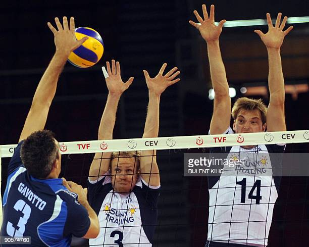 Mauro Gavotto of Italy spikes the ball over the net blocked by Finland's Mikko Esko and Konstantin Shumov during their European Volleyball...