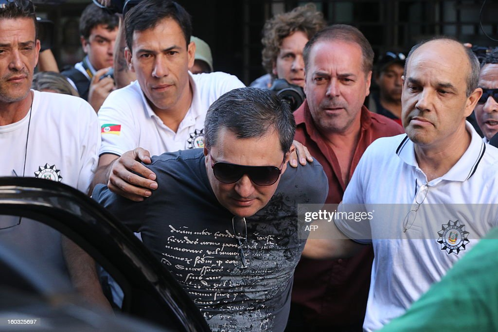 Mauro Hoffman, co-owner of the Kiss nightclub where a blaze on Sunday early morning left a death toll of over 230, is taken into custody by police in Santa Maria, southern Brazil, on January 28, 2013. Police in Brazil arrested four suspects Monday after a nightclub fire killed 231, left dozens more clinging to life, and forced officials to defend readiness for the Olympics and World Cup. Two owners of the Kiss club were arrested, along with a pair of musicians who starred in the ill-fated pyrotechnic show blamed for sparking Sunday's tragedy in the university town of Santa Maria in the south of the country. AFP PHOTO/AGENCIA RBS/Emerson SOUZA BRAZIL OUT