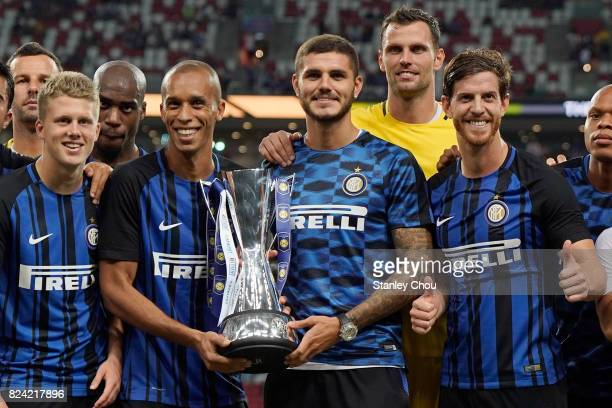 Mauro Icardi and Miranda of FC Internazionale leads his teammates to celebrate with the Champions Trophy after they defeated Chelsea FC 21 during the...