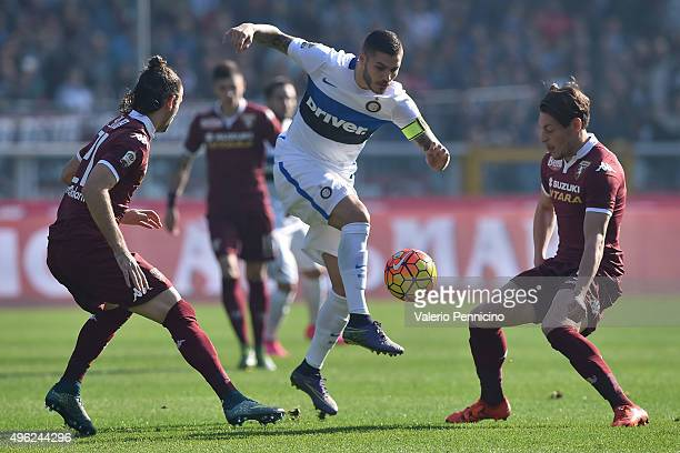 Mauro Icardi of FC Internazionale Milano is challenged by Silva Gaston and Andrea Belotti of Torino FC during the Serie A match between Torino FC and...