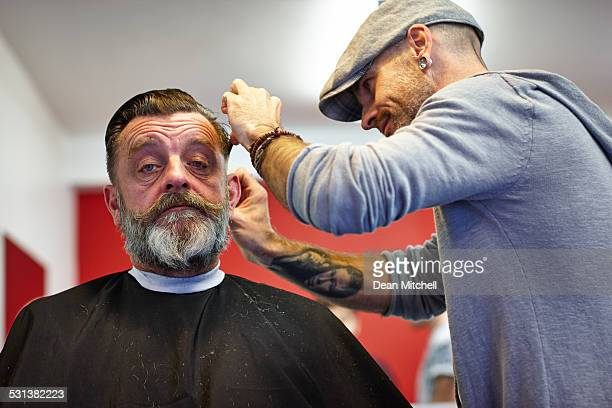 Mauture man getting a hair cut from professional hairdresser