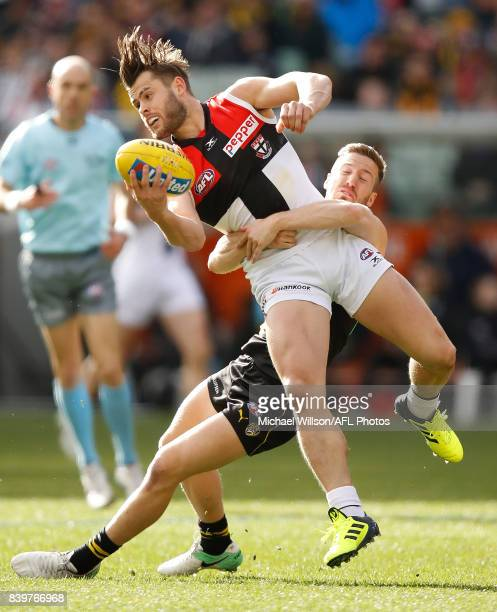 Maverick Weller of the Saints is tackled by Kane Lambert of the Tigers during the 2017 AFL round 23 match between the Richmond Tigers and the St...