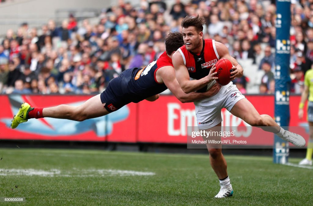 Maverick Weller of the Saints is tackled by Michael Hibberd of the Demons during the 2017 AFL round 21 match between the Melbourne Demons and the St Kilda Saints at the Melbourne Cricket Ground on August 13, 2017 in Melbourne, Australia.