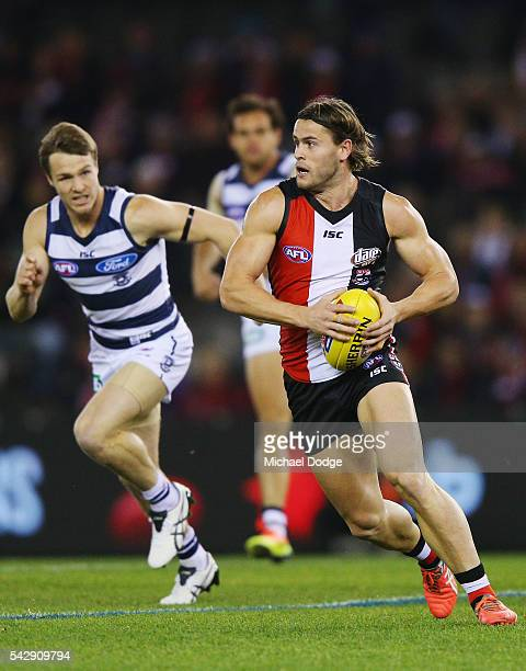 Maverick Weller of the Saints runs with the ball away from Lincoln McCarthy of the Cats during the round 14 AFL match between the St Kilda Saints and...
