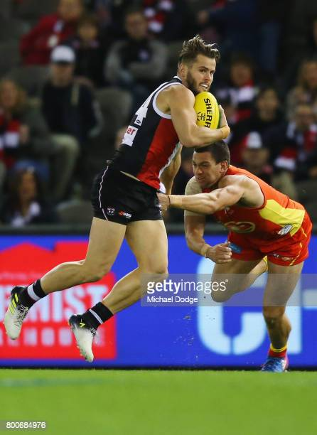 Maverick Weller of the Saints runs with the ball from Jesse Lonergan of the Suns during the round 14 AFL match between the St Kilda Saints and the...