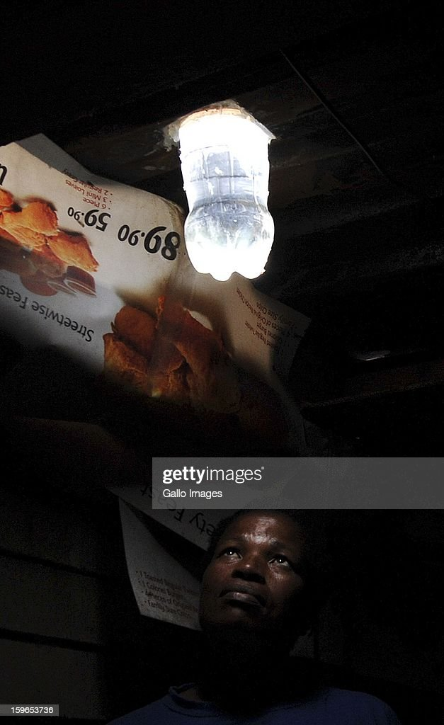 Mavis Mabaso and her son Sphsihle showing their new bottle light on January 18, 2013, in Johannesburg, South Africa. The 'Lïtre of Light' project puts plastic bottles filled with water in shack roofs, providing light to shacks with no electricity during the day.