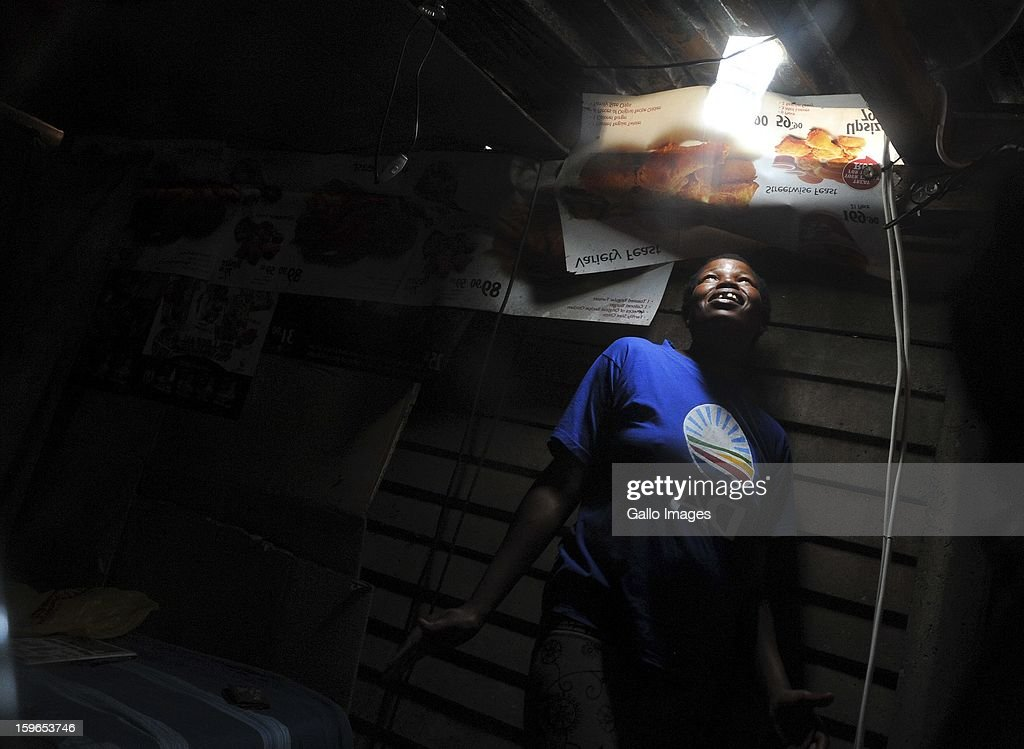 Mavis Mabaso showing her new bottle light on January 18, 2013, in Johannesburg, South Africa. The 'Lïtre of Light' project puts plastic bottles filled with water in shack roofs, providing light to shacks with no electricity during the day.